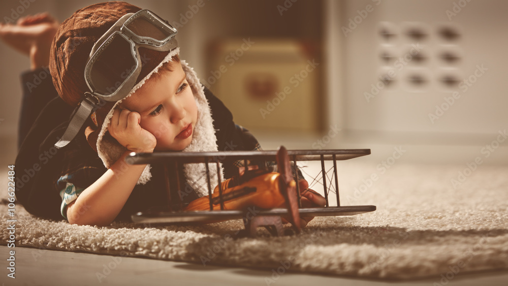 Fototapeta concept of dreams and travels.  pilot aviator child with a toy a