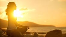Woman Meditating In Lotus Pose On Beach At Sunset