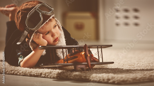 Fotografiet concept of dreams and travels.  pilot aviator child with a toy a