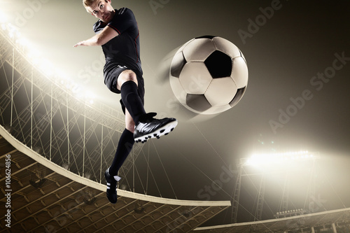 Athlete kicking soccer ball in stadium