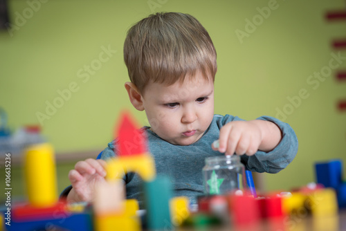 Foto  Boy playing with toys in nursery
