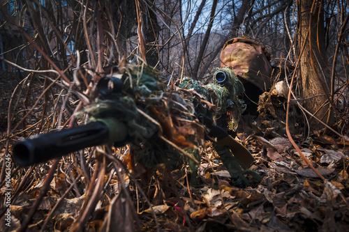 Fotografía  Francotirador el uso de traje de camuflaje con esconder el rifle en el bosque