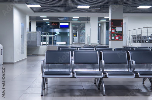 Poster de jardin Aeroport Waiting zone in an airport with grey chairs.
