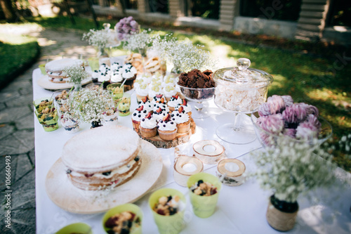 Poster Dairy products Delicious wedding reception candy bar Dessert table for a wedding outdoor party. Ombre cake, cupcakes, sweetness and flowers