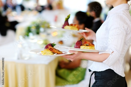 Fotografie, Obraz  Waitress carrying three plates with meat dish