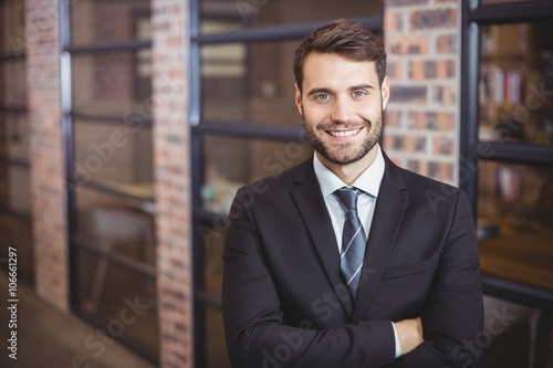 Handsome businessman with arms crossed standing in office Canvas