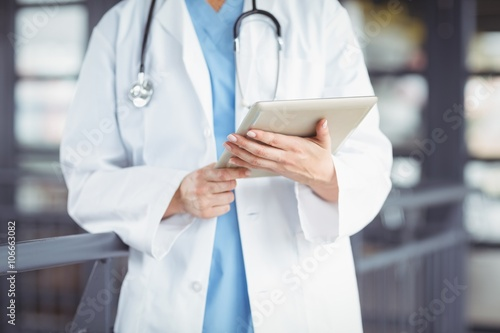 Midsection of doctor holding digital tablet Poster