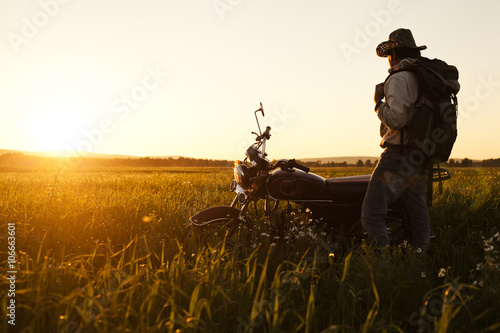 Mari man standing in field with motorcycle