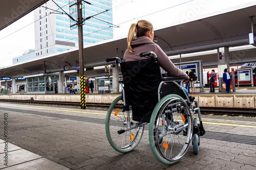 Fotografia  Frau sitzt in einem Rollstuhl auf einem Bahnhof