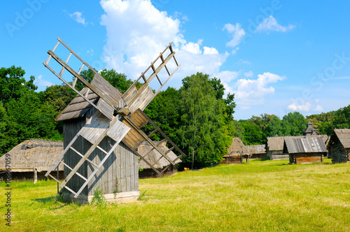 Poster Molens old wooden windmill in a field