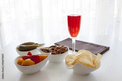 Foto op Plexiglas Voorgerecht Aperitivo con patatine, cetrioli, peperoni, bretzel