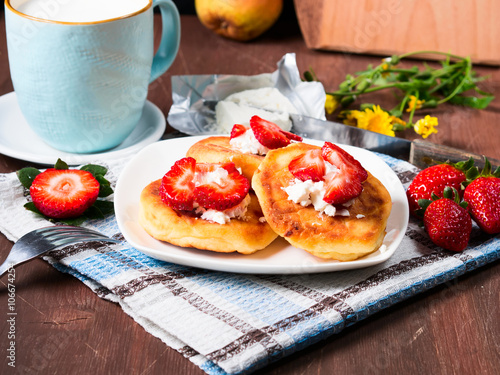 Breakfast with cottage cheese pancakes with cream cheese and strawberries and a cup of milk