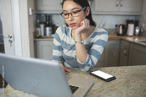 Young woman using a laptop in the kitchen Poster