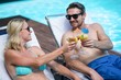 Couple sitting on sun lounger toasting cocktail