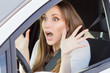 Frightened young car driver woman look straight