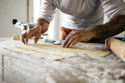 Fotografia  Making ravioli on a wooden table and tools