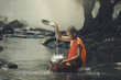 Monk playing with water in river