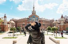 Spain, Barcelona, Back View Of Woman Looking At Sant Pau Art Nouveau Site