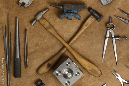 plakat Tools of jewellery. Jewelry workplace on leather background. Hammers, anvil. Top view.