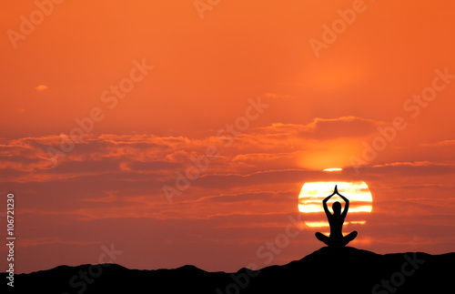Papiers peints Corail Sunset landscape with girl practicing yoga on the background of sun and red sky in the hill in summer