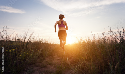 Spoed Foto op Canvas Jogging Young sporty girl running on a rural road at sunset in summer field. Lifestyle sports background
