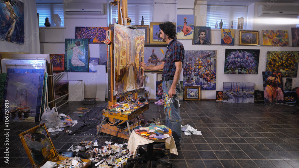 Fototapety, obrazy: In the process of creating a masterpiece. A professional artist working in his studio.