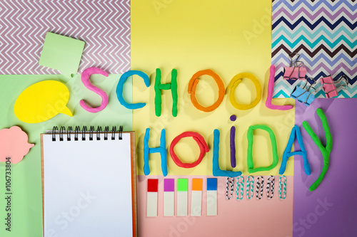 Valokuva  Inscription SCHOOL HOLIDAY made of colorful plasticine and stationery on sheets