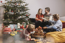 Family Of Four Unwrapping Christmas Gifts And Playing With Noah's Ark