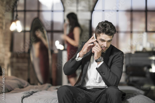 Elegant man on bed on the phone with wife in background