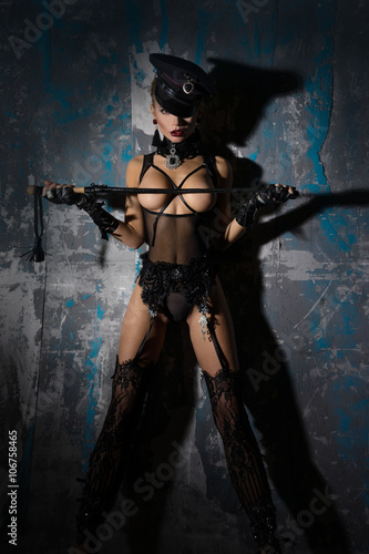 Fotografering  Girl in fetish - image, standing with a whip near a wall