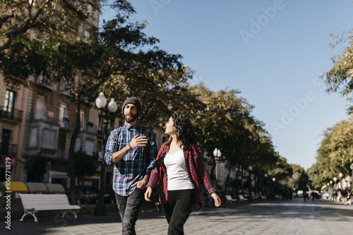 Spain, Tarragona, young couple walking in the city