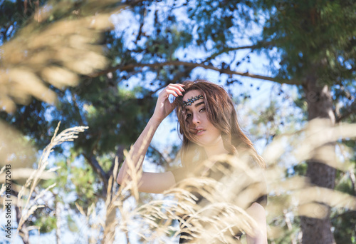 portrait of young lady in black through grass Canvas Print