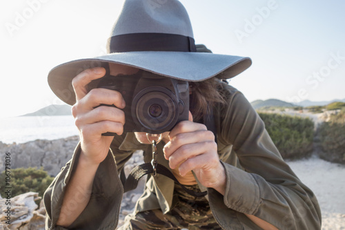 Spain, Ibiza, photographer wearing floppy hat taking a picture