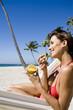 femme à la plage dans un hamac mangeant un fruit