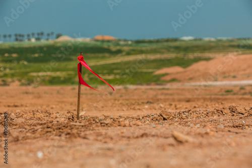 Fotografija Metal survey peg with red flag on construction site