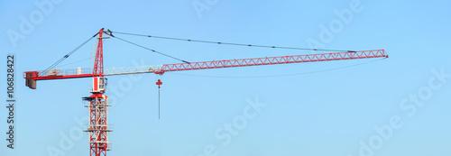 Fotografia  Red and white building tower crane against a blue sky. Jib crane