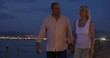 Steadicam shot of mature couple having romantic walk on the beach in the evening and taking selfie shot at smartphone.