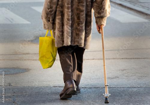 Fotografie, Obraz  Frau mit Einkaufstasche und Gehstock