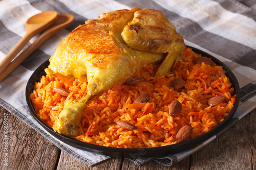 Arabic food: kabsa with chicken and almonds close-up on a plate. Horizontal