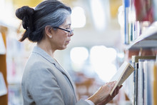Older Hispanic Woman Reading Book In Library