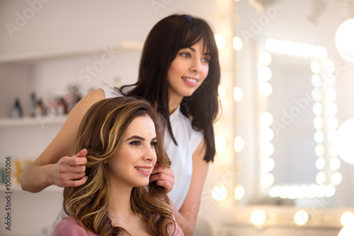 Positive professional hairdresser working on the salon