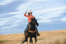Caucasian Woman On Horse Throwing Lasso In Grassy Field