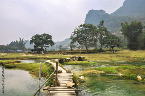 Wooden footbridge over the water of the river - 106866057