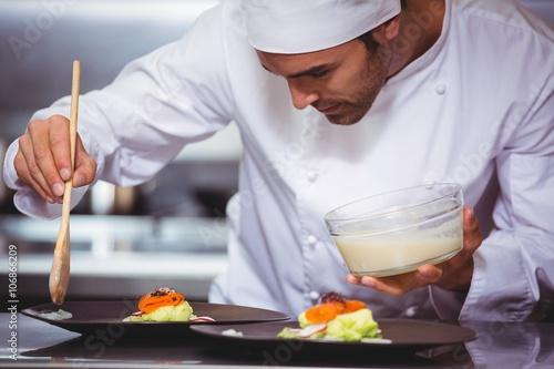 Fotografie, Obraz  Chef putting sauce on a dish