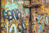 Stara zardzewiała brama z graffiti
