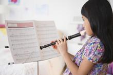 Vietnamese Girl Playing Recorder From Sheet Music