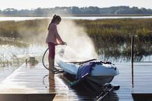 Caucasian Girl Spraying Canoe On Wooden Dock Over Lake