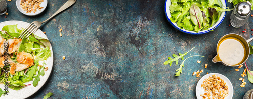 Healthy lunch eating with Chicken salad , pine nuts and oil dressing. Chicken salad with green leaves served on rustic background, top view, place for text, banner