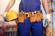 construction worker with tools belt at building site