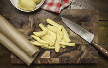 Still Life Of Peeled And Sliced Potatoes, Kitchen Knife On Chopping Board